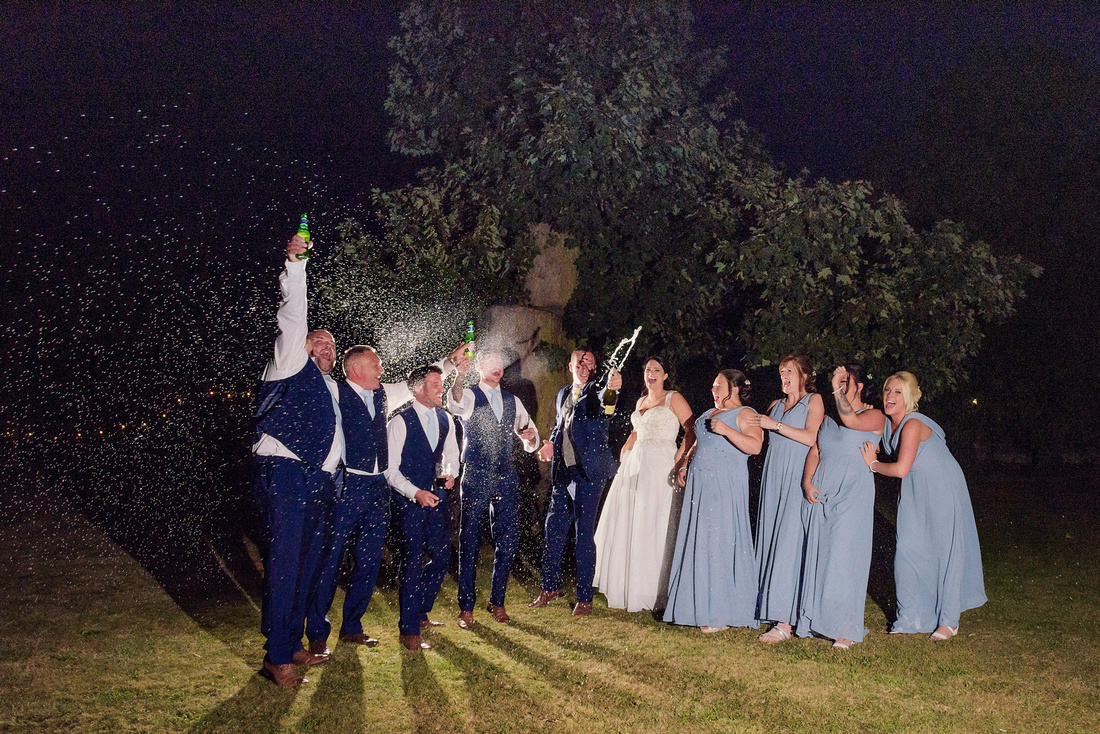 Night time, bridal party, celebrating, champagne, happy bridesmaids and groomsmen popping the cork
