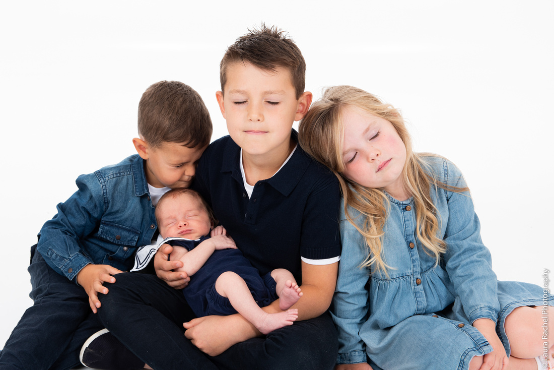 Siblings and cousins holding a baby for a photo