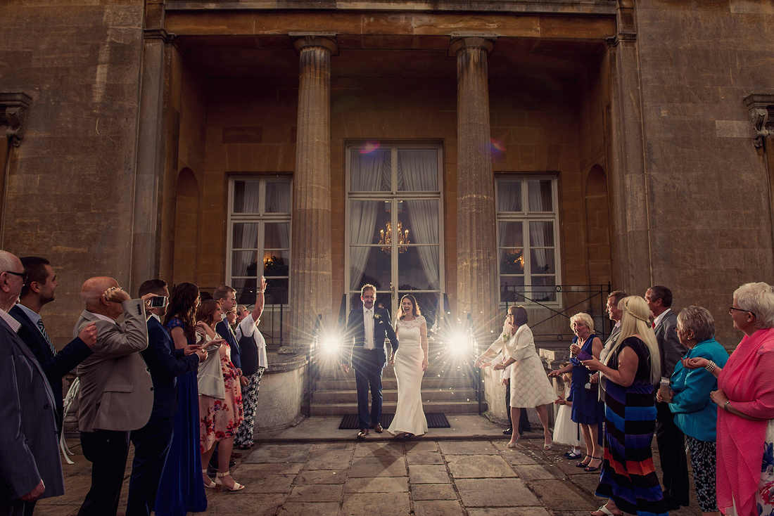 Bride and Groom walking out of Luton Hoo with confetti