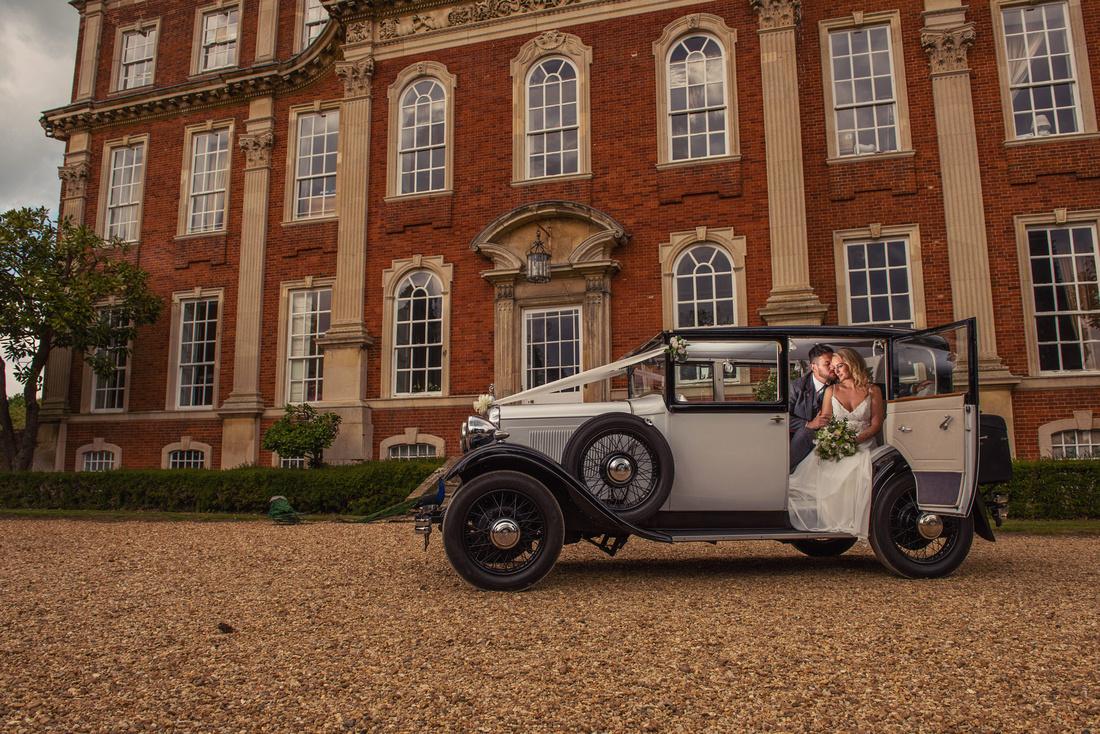 Bride and Groom sitting in the wedding car outside Chicheley Hall Milton Keynes