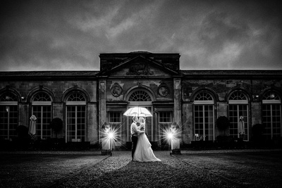 Bride and Groom outside Woburn Sculpture Gallery with umbrella and flash